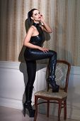 stock photo of catsuit  - Sexy woman in black latex catsuit posing at vintage wall step on chair desire - JPG