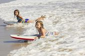 picture of boogie board  - Cute little girls boogie boarding in the ocean waves - JPG