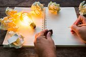 picture of understanding  - Hand write over Note book and light bulb on wood table - JPG