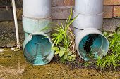 foto of downspouts  - Modern plastic drain pipe with flowing rain water - JPG