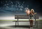 stock photo of sitting a bench  - Young woman sitting on bench and playing violin - JPG