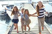 foto of marines  - Group of 4 fashion kids wearing striped navy clothes in marine style running in the sea port - JPG