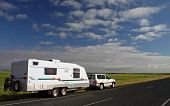 stock photo of nomads  - Offroad caravan and 4WD on tour in the Australian outback against a brilliant green grassy plain and blue sky with interesting clouds - JPG
