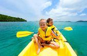 foto of paddling  - Kids enjoying paddling in colorful yellow kayak at tropical ocean water during summer vacation - JPG