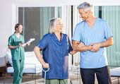 picture of male nurses  - Happy male nurse assisting senior woman to walk with caretaker in background at nursing home yard - JPG