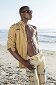 picture of hot pants  - Handsome tall muscular African American man wears dark shades while posing with fashionable shirt and pants displaying half torso and abs on sunny beach - JPG