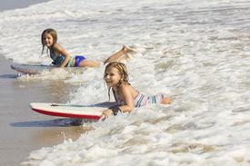 foto of boogie board  - Cute little girls boogie boarding in the ocean waves - JPG