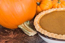 stock photo of pumpkin pie  - Closeup of pie pumpkin and a homemade pumpkin pie wooden background  - JPG