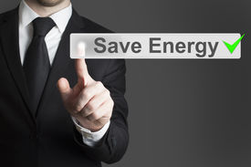 stock photo of save earth  - businessman in black suit pushing flat touchscreen button save energy eco mode - JPG