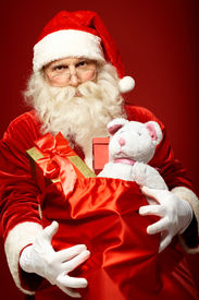foto of generous  - Portrait of generous Santa Claus holding presents in big red sack - JPG