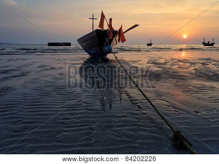 The fishing boat stuck on sand beach Thailand