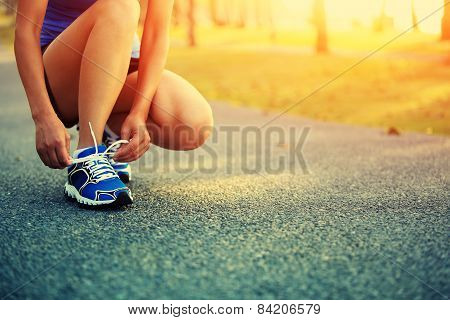 young woman runner tying shoelaces on stairs