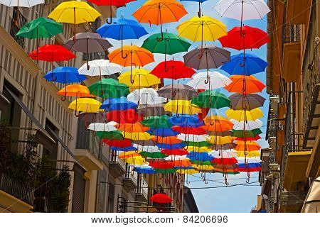 Colorful umbrellas installed on the street in Spanish city.
