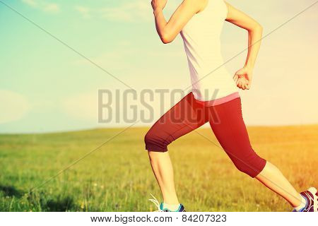 unner athlete running on grass seaside. woman fitness jogging workout wellness concept.