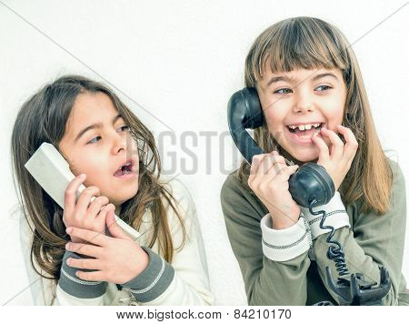 Two Seven Year Old Girls Talking On The Old Vintage Phones With The White Background