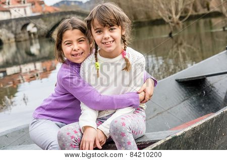 Two Sisters Are Sisters Are Sitting In The Boat And Hugging