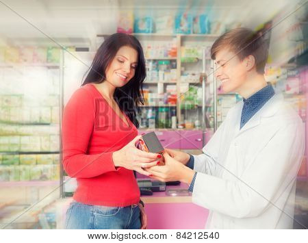 Smiling Pharmacist Showing A Box To Client