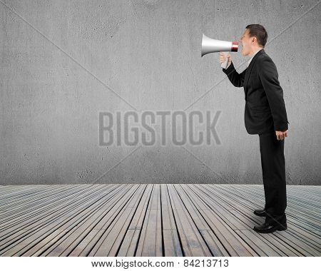 Business Man Using Megaphone Yelling With Concrete Wall Wooden Floor