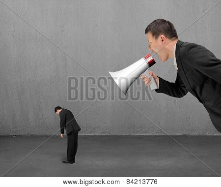 Businessman Using Megaphone Yelling At His Employee With Concrete Room