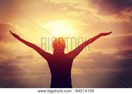 young woman open arms under the sunrise at seaside