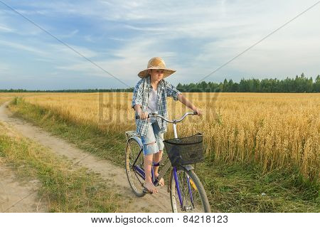 Teenager Boy Riding A Bicycle On Country Road