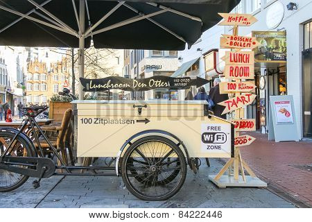 People Walk Past The Carriage For Fast Food, Parked Near The Restaurant  In The Dutch Town Den Bosch