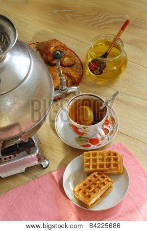 Tea From A Samovar, With A Lemon, Honey, Rolls And Cakes