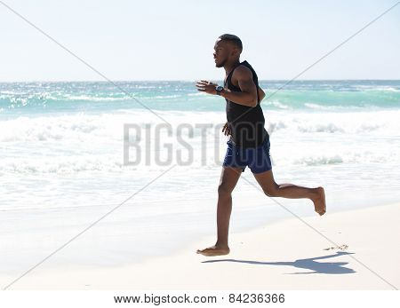 Young Man Running Barefoot At The Beach