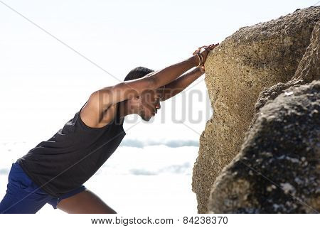 Healthy Young Man Pushing Against Rock