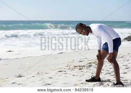 Young Man Standing On Beach With Hands On Knees