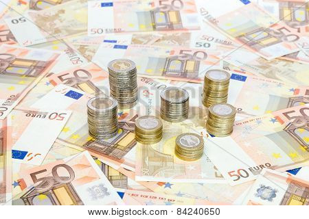 Piles of euro coins standing on euro notes