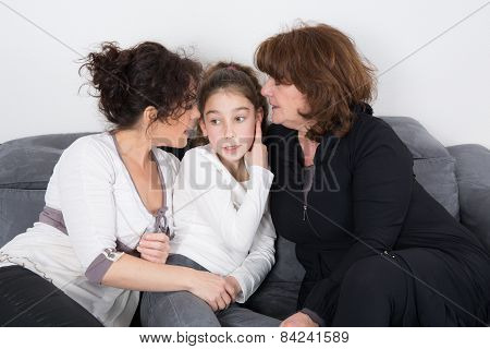 A Cheerful Grandmother With Her Daughter And Her Granddaughter Indoors