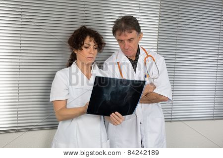 Two Doctors Looking At X-ray .