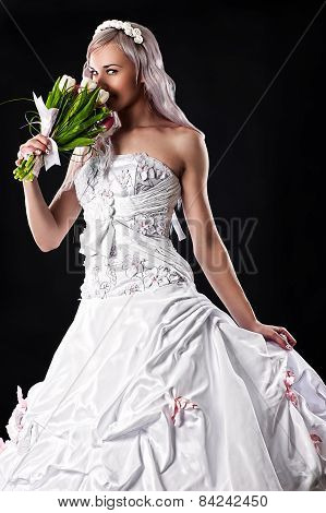 beautiful bride smelling a wedding bouquet of tulips