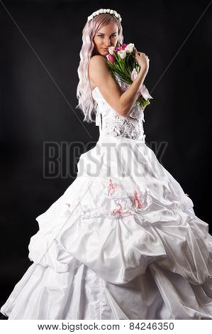 attractive bride smelling a wedding bouquet of tulips