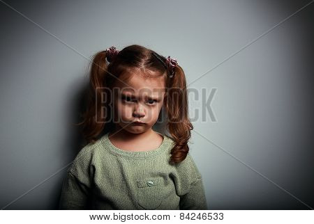 Sad Kid Girl Looking With Very Unhappy Face On Dark