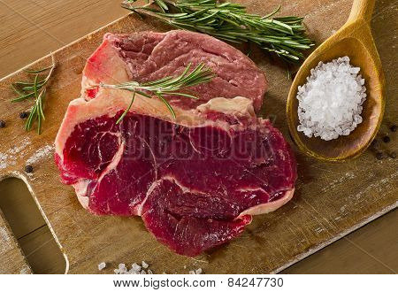 Raw Beef T-bone Steak On  Old Wooden Board