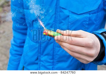 Hand holding burning firework in front of blue jacket