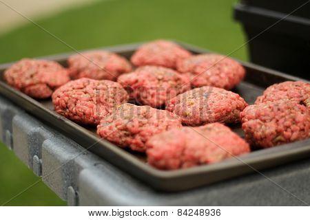Raw Hamburger Patties at the Grill