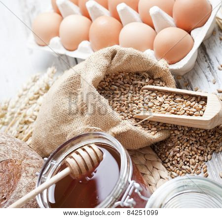 Freshly baked bread rolls,eggs, wheat ears and honey