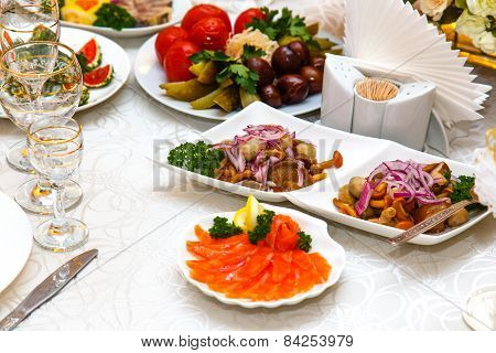 Salad With Mushrooms, Pickled Cucumbers And Tomatoes And Sliced Fish On Banquet Table