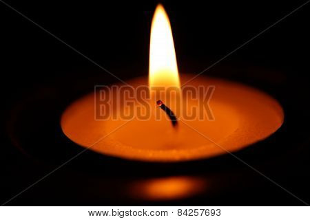 Candle on dark background.