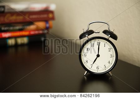Vintage alarm clock on dark brown surface. Shows 7 o'clock. Pile of books in background.