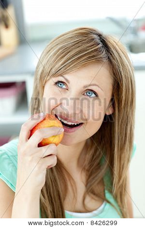 Captivating Caucasian Woman Eating An Apple In The Kitchen