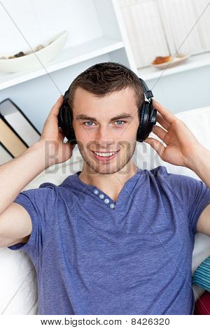 Relaxed Young Man Listening To Music Looking At The Camera