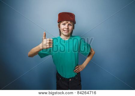 Muslim boy of ten years,  skullcap, thumbs  up on a gray backgro