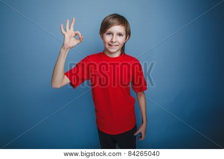boy teenager European appearance in a red shirt showing sign all