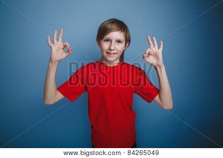 boy teenager European appearance in a red shirt showing sign yes