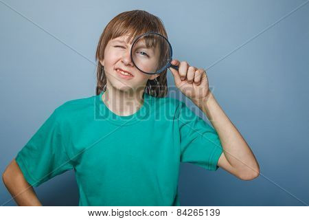 boy teenager European appearance in a green shirt looking throug