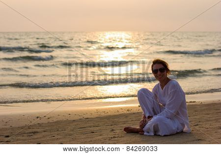 Nice lady at the beach spending sunset time